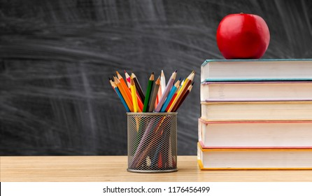 Back to school background with books and apple over blackboard