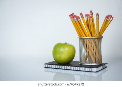 Back to school background on white table as a background. Books, pencils and apple on desk. First time to school. Elementary school