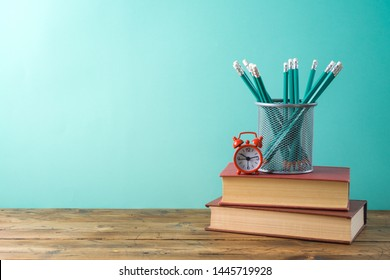 Back to school background with pencils, alarm clock and books on wooden table