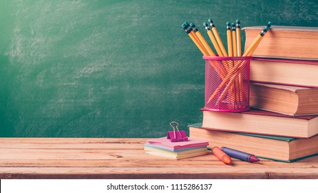 Back to school background with pencils and old books over chalkboard