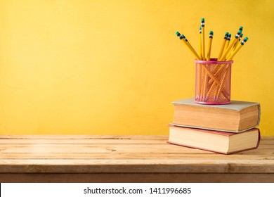 Back to school background with pencils and old books on wooden table over yellow wall