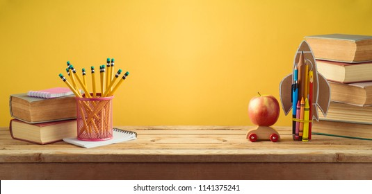Back to school background with rocket made from pencils, apple and old books over yellow wall