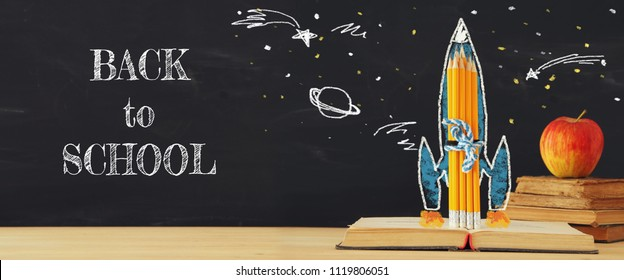 Back to school banner. rocket sketch and pencils over open book in front of classroom blackboard