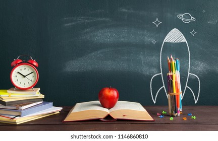 Back to school banner. Rocket sketch and open book in front of blackboard