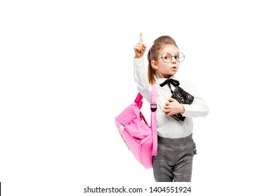 Back to school. Beautiful little girl dressed like a School girl - in white shirt and gray pants, rounded glasses, hold a book, school bag and posing like model points finger up. Isolated on white.