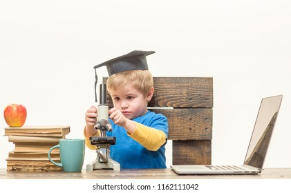Back to school. Biology lesson and study at laboratory with microscope. Home schooling. Science, biology, experiment, education, modern technology concept. Little kid in graduation hat with microscope