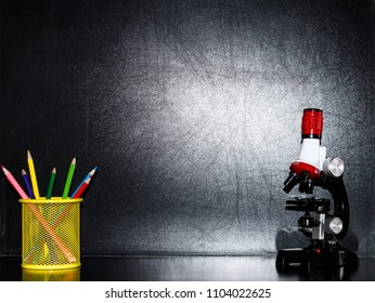 Back to school black  background with blackboard, colorful pencils and a microscope