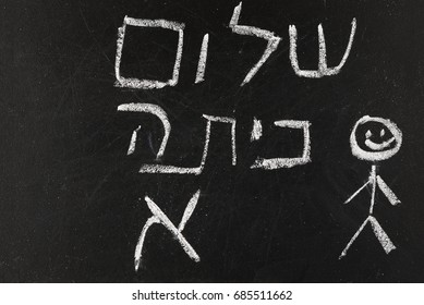 Back to School. Blackboard/ chalkboard with Hello First Grade / class greetings in Hebrew (Shalom Kita Alef)  written with white chalk on the black board. Photo.