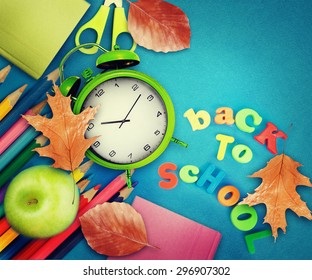 Back to school - blackboard with school equipment on table.