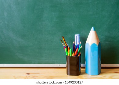 Back to school. Blue decorative pencil and pens, pencils, brushes in a glass against the background of a green blackboard. School background with space for your text