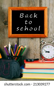 Back to school. Books and school tools on a wooden shelf. A wooden background.