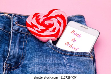 back to school with candies and mobile phone in the blue jeans pocket