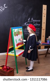 Back to school! Cheerful little girl is standing near the school board. School concept. Schoolgirl answers at lesson. The kid is studying in the classroom on the background of the school board.