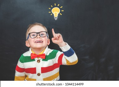 Back to school. School child in elementary school with lightbulb on blackboard. Funny child in class with copy space. Success, bright idea, creative ideas and innovation technology concept.