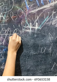 Back to school. A child paints scribbles by chalk on a board