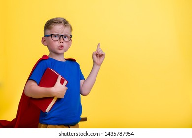 Back to school. Child playing superhero with book in hands. Kid in glasses has idea. Boy isolated on yellow blackboard. Success, bright idea, creative ideas and innovation technology concept.