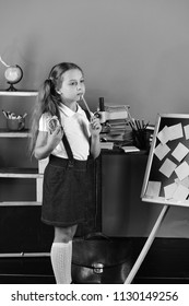 Back to school and childhood concept. Kid and school supplies on green wall background. Girl stands by blackboard with sticky notes and holds green clock and pencil. Schoolgirl with thoughtful face