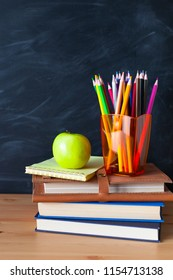 Back to School cocept. Still life with school books, pencils and apple against blackboard background. Close up