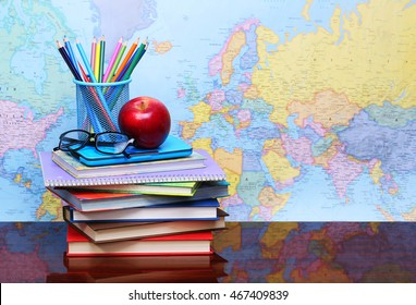 Back to school concept. An apple, colored pencils and glasses on pile of books on desk over map