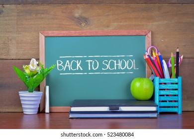 Back to School concept with apple on table in front of chalkboard