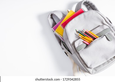 Back to school concept. Backpack with school supplies, pens, pencils, notebook on white background. Flat lay, top view, copy space
