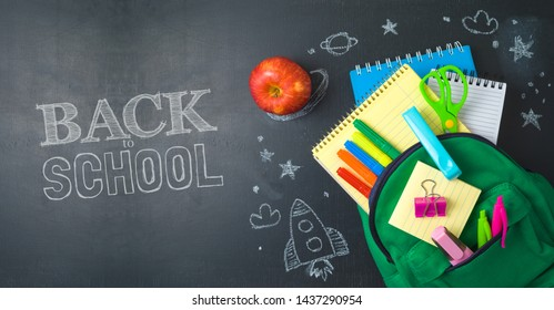 Back to school concept with bag backpack and school supplies over chalkboard background. Top view from above