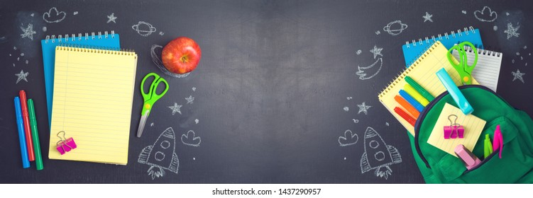 Back to school concept with bag backpack, notebook and school supplies over chalkboard background. Top view from above