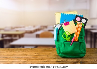 Back to school concept with bag backpack and school supplies on wooden table over classroom background
