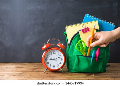 Back to school concept with bag backpack and school supplies  over chalkboard background