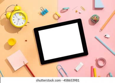Back to school concept. Blank tablet with school and office supplies on office table. Flat lay with copy space.
