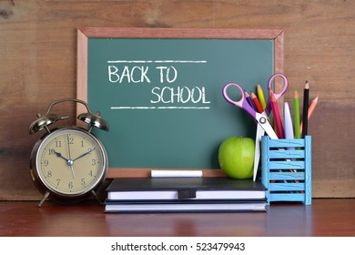 Back to school concept with books and alarm clock with chalkboard