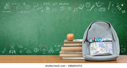 Back to school concept with school books, textbooks, backpack and stationery supplies on classroom desk with teacher's chalkboard background with educational doodle for new academic year begin