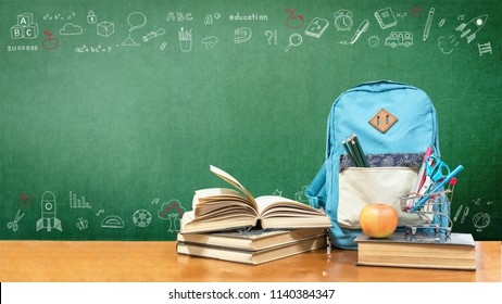 Back to school concept with school books, textbooks, backpack and stationery supplies on classroom desk with teacher's green chalkboard background with educational doodle for new academic year begin