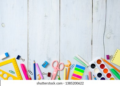 Back to school concept, border frame of colorful stationery supplies for teaching kids drawing on empty white wooden desk. Creative education setting, kids desk top view, flat lay, copy space