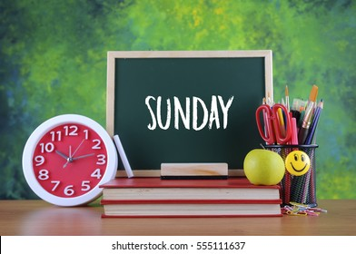 Back to school concept with chalkboard, alarm clock, colorful stationery and books with text SUNDAY