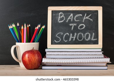 Back to school concept with chalkboard, books and pencils