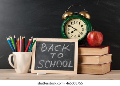 Back to school concept with chalkboard, books, alarm clock and pencils