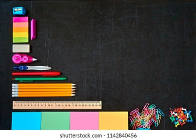 Back to school concept. Colorful school office supplies on black background. Copy space. Place for text.