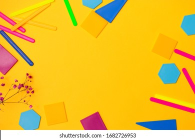 Back to school concept flat lay.Color counting sticks and plastic geometric shapes on the yellow background.Copy space for text,top view