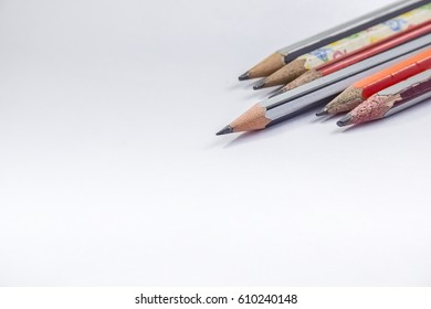 Back to school concept - Go Ahead - a Pencil,erasor, sharpner an cut slice of the pencil on white table with or without spectacles not properly aranged isolated.
