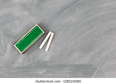 Back to school concept with green erased chalkboard and eraser plus chalk
