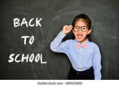 back to school concept with happy cheerful small teacher in chalk blackboard background.