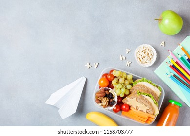 Back to school concept. Healthy lunch box and colorful stationery on table top view.