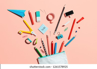 Back to school concept, illustration. Pencil case with various stationery on yellow desk - flat lay.