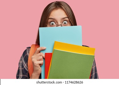 Back to school concept. Image of surprised emotive European woman hides behind books, has eyes popped out, wears round transparent glasses and checkered shirt, stands against pink background.