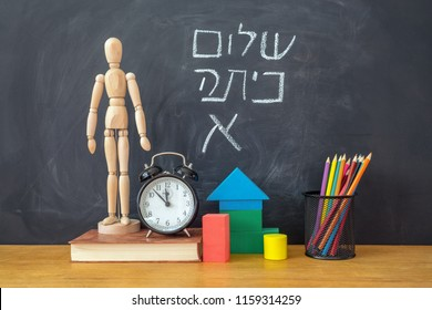 Back to school concept. The inscription in Hebrew Back to school on chalkboard background.