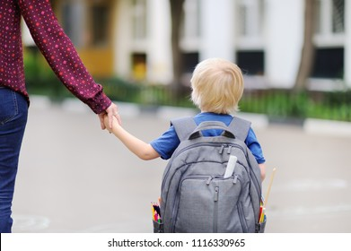 Back to school concept. Little pupil with his young mother. First day of primary school. Education for small kids.