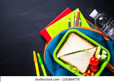Back to school concept. Lunch box, stationery and backpack.