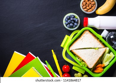 Back to school concept. Lunch box with stationery on black.