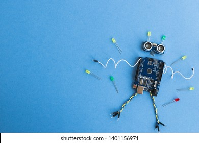 Back to school concept. A metal robot and an electronic board that can be programmed. Robotics and electronics. DIY robotics. STEM and STEAM education for kids. Free space for text. - Shutterstock ID 1401156971